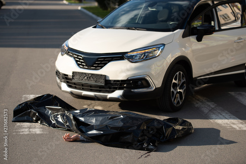 high angle view of dead body and automobile on road after