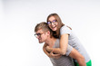 Education, funny people and joke concept - a young woman jumped on a back of man. They are happy