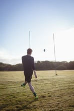 Rugby Player Kicking Rugby Ball In The Field
