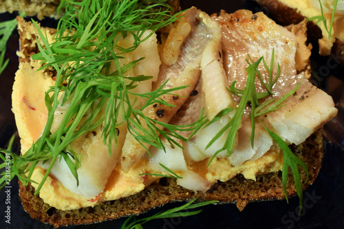 Poster Picnic Open rye sandwich with fried perch fish, cream cheese and dill. Close up top view.
