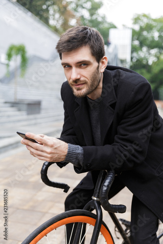 Handsome young man dressed in coat leaning on a bicycle