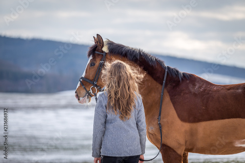 Attractive young girl looking on her horse in the snowy field