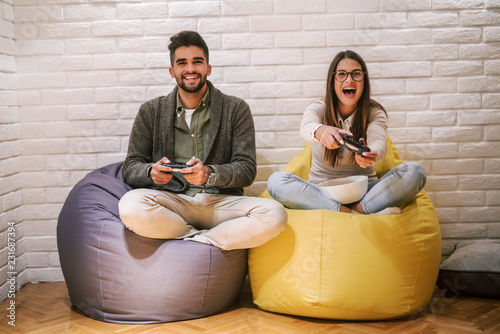 Couple playing video game while sitting with crossed legs on lazy bag Wallpaper Mural