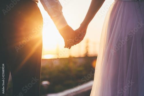 Fotografie, Obraz  Bride and groom holding hands closeup