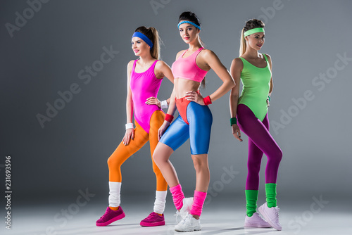 attractive sporty girls in 80s style sportswear posing together on grey Canvas Print