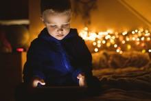 Boy In Blue Jacket Using Digital Tablet Against Christmas Lights