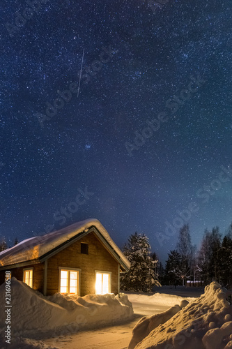 Winter landscape with wooden house under a beautiful starry sky