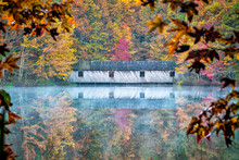 Covered Bridge In The Fall, As Mist Rises From The Calm Waters, Fall Colors Are Reflected Around The Covered Bridge.