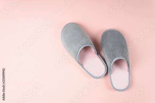 Gray and pink home slippers on a pastel paper background. Top view. Copy space. Toned