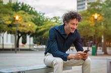 Mature Man Sitting On Bench Using Phone