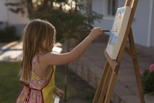 Girl Painting On Canvas In Garden
