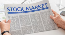 Man Reading Newspaper With The Headline Stock Market