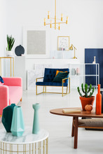 Real Photo Of Geometrical Vases On A Table With A Wide Armchair In The Background In A Living Room Interior