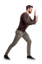 A Bearded Fit Man In Casual Pants Presses His Hands Over An Invisible Object In Order To Move It.