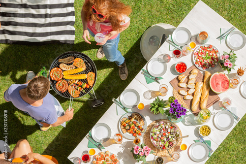Photo Stands Grill / Barbecue High angle on man and woman grilling shashliks next to table with food in the garden