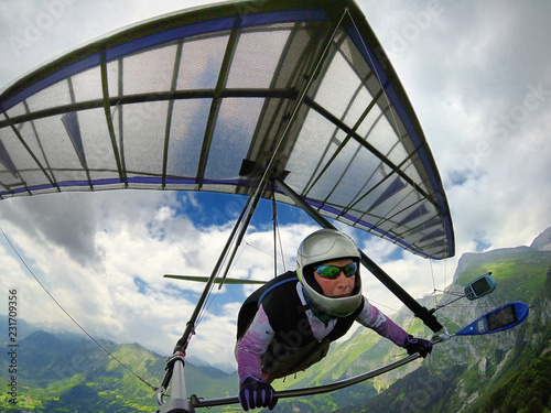 Aerial shot of brave extreme hang glider pilot soaring the thermal updrafts above mountains
