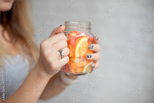 Close-up happy woman with glass of fresh summer lemonade with straw. Caucasian young girl 20-25 years old indoors against brick wall background.