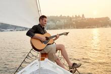 Man Playing Guitar On A Sailbo...