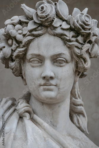 Commemoratif Statue of sensual busty and puffy renaissance era woman in circlet of flowers, Potsdam, Germany, details, closeup
