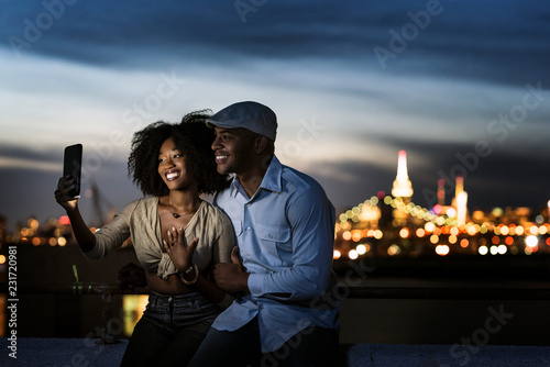 Couple taking a selfie on a terrace with the New York City skyline in the background