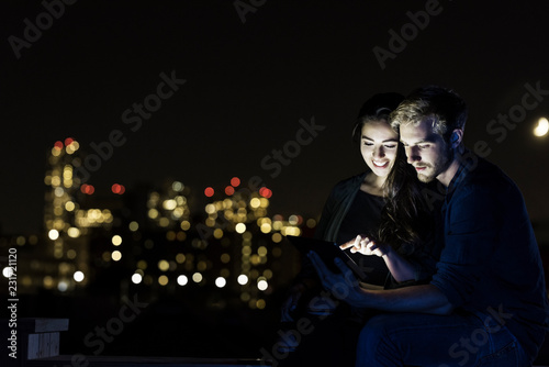 Man and woman using a tablet on a rooftop at night in the city