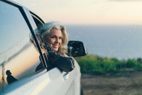 Woman smiling while leaning on car window at countryside