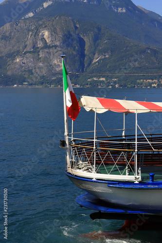 Fotografía  traghetto con bandiera italiana sul lago di como, ferry boat with Italian flag o
