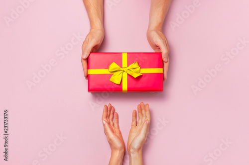 Photo  Top view of male and female hands holding red gift box with golden ribbon on pink background Flat lay