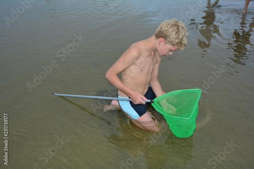 Fotografie, Obraz  Blonder Junge sitzt im seichten Wasser am Strand mit einem Fischernetz - Käscher