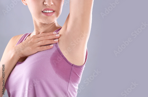 Young woman with sweat stain on her clothes against grey background, space for text Fototapeta