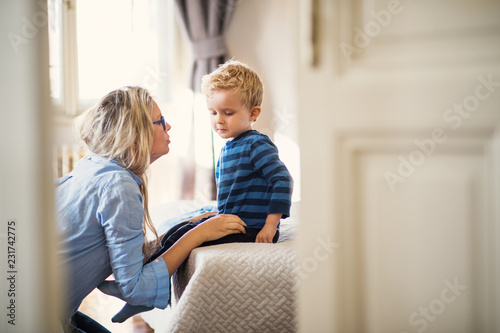 A young mother talking to her toddler son inside in a bedroom. Canvas Print