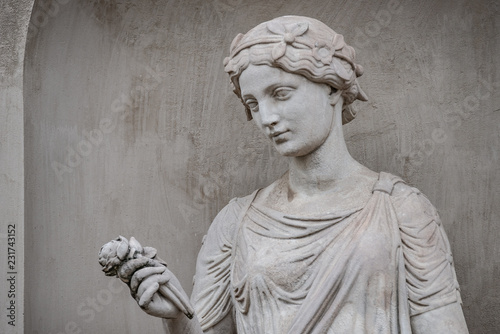 Photo sur Toile Commemoratif Ancient statue of sensual Greek renaissance era woman with a flower, Potsdam, Germany, details, closeup