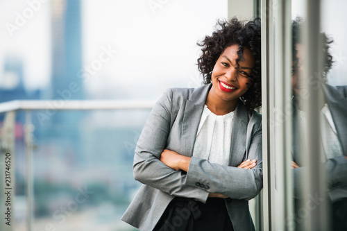 Obraz A portrait of a businesswoman standing on a terrace, arms crossed. - fototapety do salonu