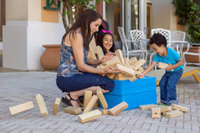 A Mother Tries To Grab The Collapsing Block Tower While Playing With Kids.