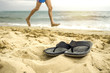 pair, two of men's beach slippers on the sand on the beach by the sea or ocean, feet running man