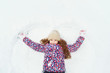 Little girl on a snow showing angel figures.
