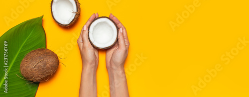 Ripe coconut in female hands and tropical leaves on yellow colored background minimal flat lay top view. Pop art design creative summer, food concept. Tropical fruit whole and half abstract background