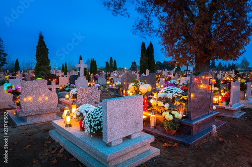 Colorful candles on the cemetery at All Saints Day, Poland Fototapeta