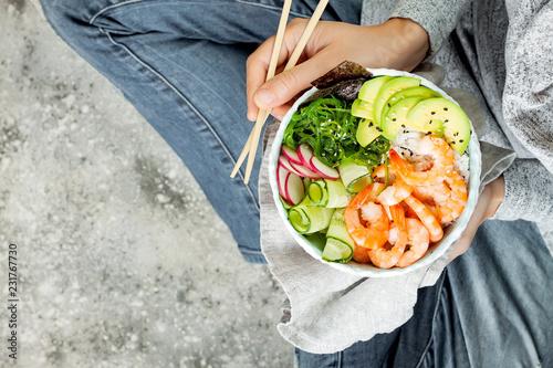 Foto op Canvas Kruidenierswinkel Girl in jeans holding shrimp poke bowl with seaweed, avocado, cucumber, radish, sesame seeds.