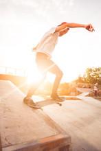 Male Teenager Performing Skateboard Tricks Against Golden Sunset