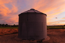 Grain Silo Against An Orange And Blue Sunset Sky In Montana.
