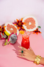 Hand Holding Cosmopolitan Cocktail Next To Dragonfruit And Pomelo