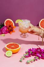 Hand Holding Paloma Cocktail Next To Grapefruit