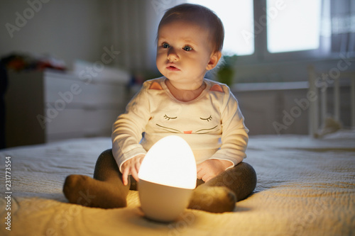 Adorable baby girl playing with bedside lamp in nursery Canvas Print