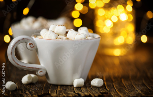 Hot chocolate with marshmallows against background with beautiful Christmas lights of bokeh