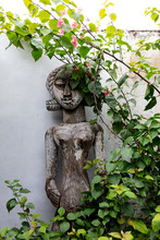 Statue Of A Woman Surrounded By Plants