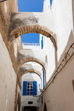 Building Arches Leading A Window With Blue Shutters