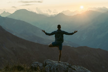 Young Man Practicing Yoga. He Is Stretching And Feels Relaxed At Sunset In The Swiss Alps