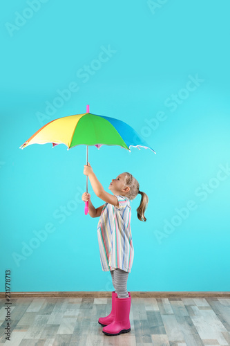 Little girl with rainbow umbrella near color wall
