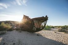 Rusting Hulk Of Abandoned Trawler In Desert At Sunset
